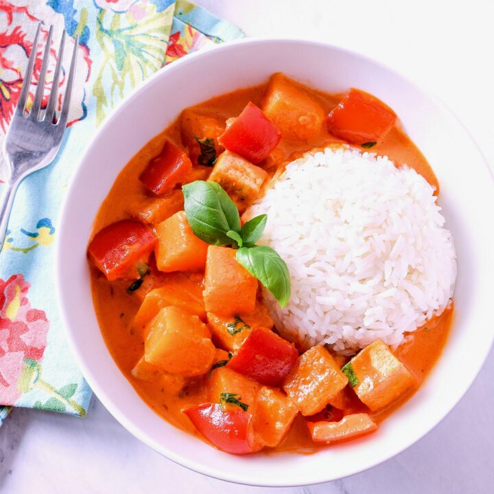 A bowl of pumpkin curry served with a scoop of rice, napkin, and fork.