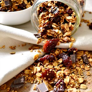 A jar of chocolate covered cherry granola on a table.