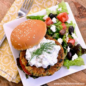 A Greek Veggie Burger on a plate with a salad.