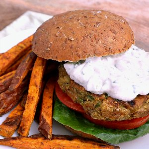 An Indian Spiced Quinoa Chickpea Burger on a plate with sweet potato fries.