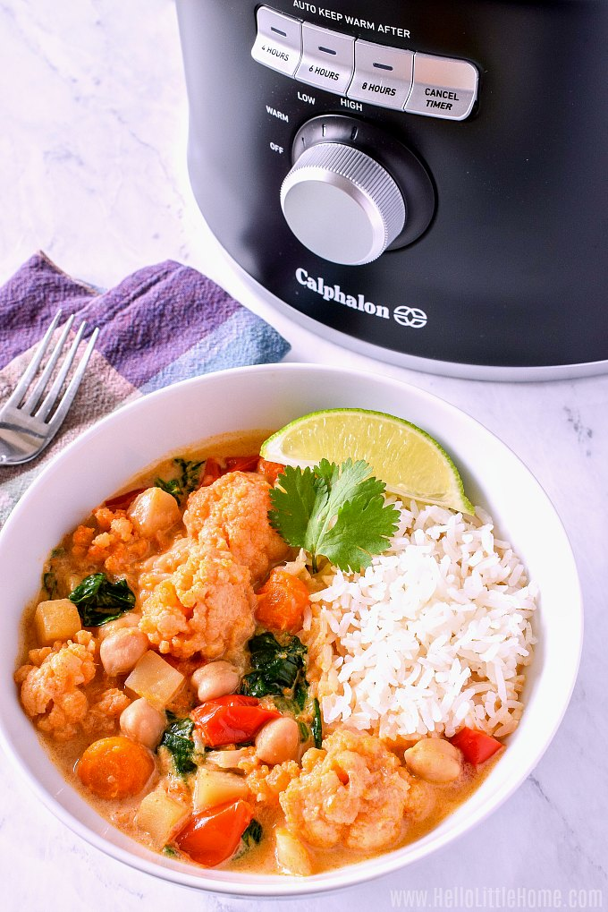 A bowl of Slow Cooker Veggie Curry with a slow cooker in the background.