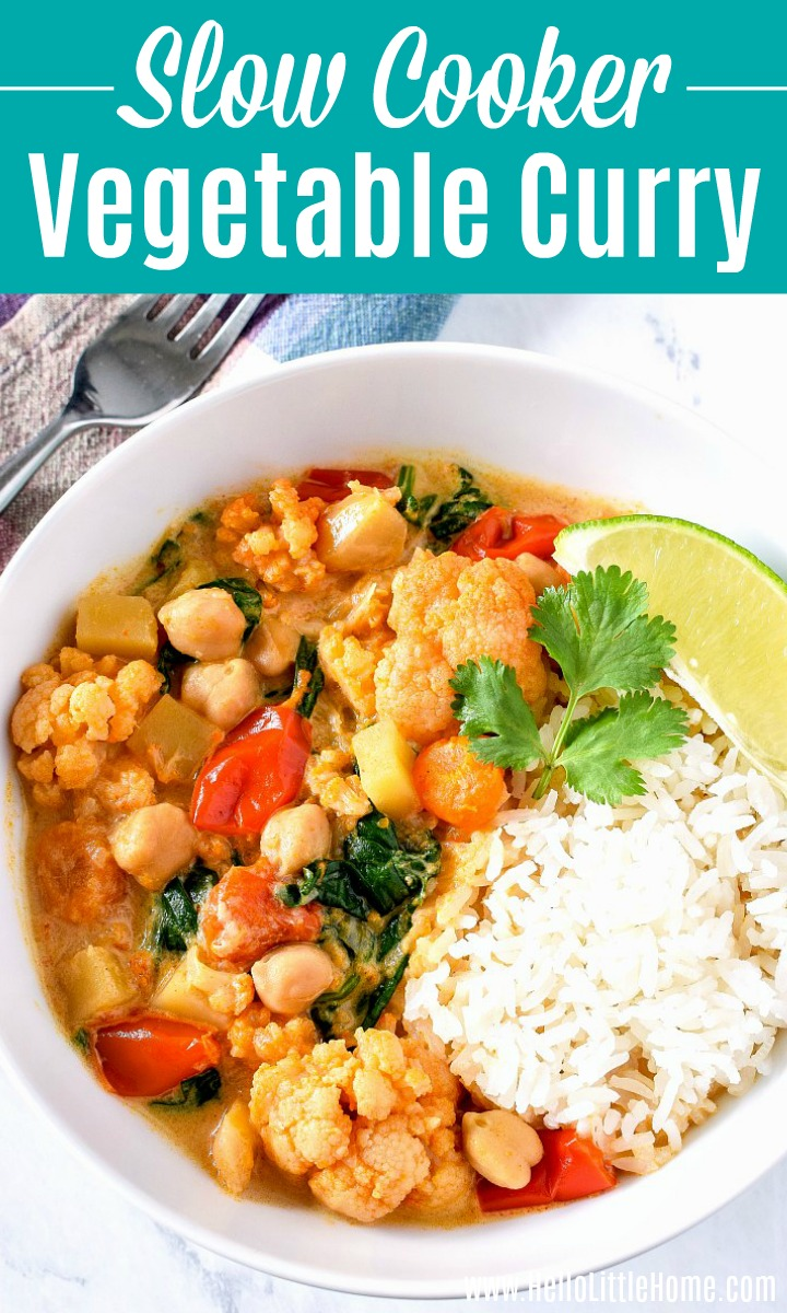 Slow cooker vegetarian curry in a bowl with rice, cilantro sprig, and a lime wedge.