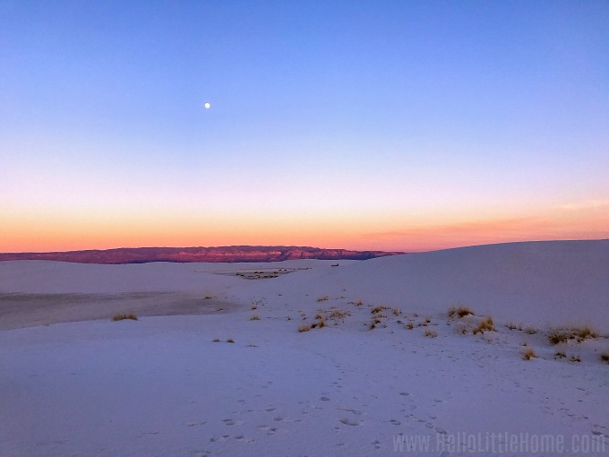 A glowing sunset with a full moon in White Sands New Mexico.