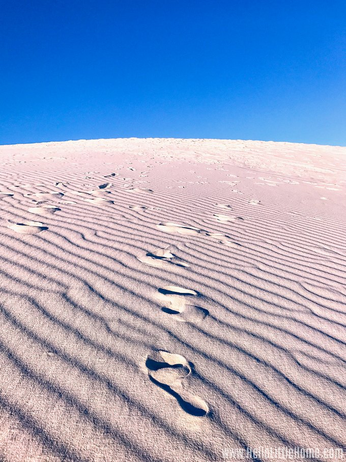 A giant sand dune with foot steps imprinted in White Sands National Monument New Mexico.