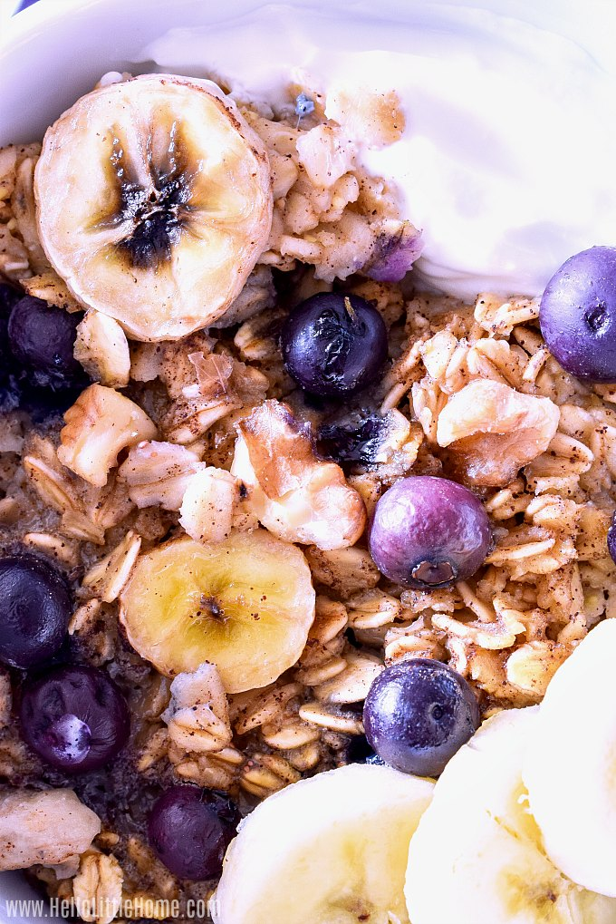 Closeup of a bowl of Blueberry Baked Oatmeal with bananas, yogurt, and nuts.