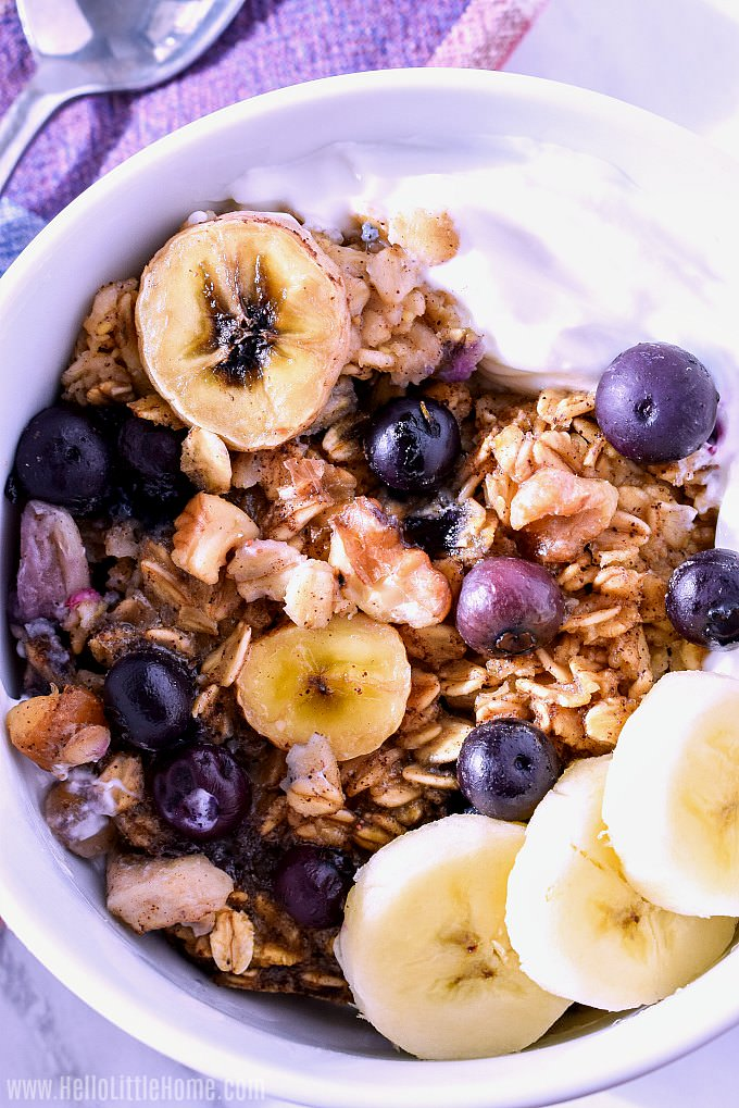 A bowl of Baked Oatmeal served with yogurt and fresh fruit.