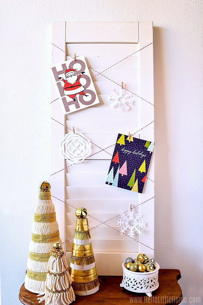 A DIY Christmas Card Holder on a table with homemade Christmas trees.