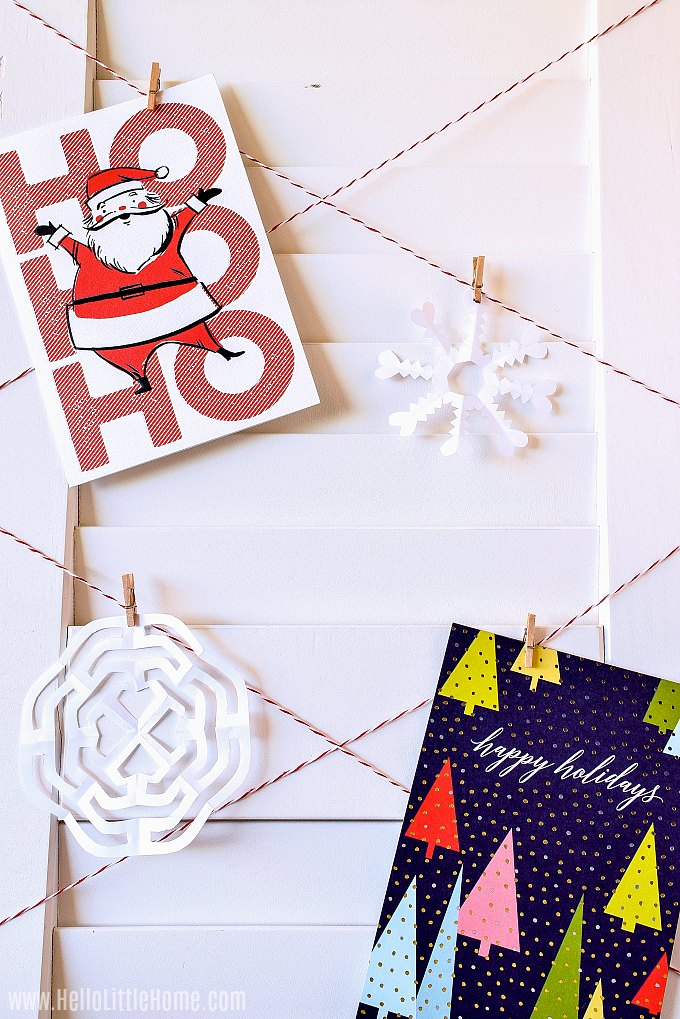Cards and homemade snowflakes on a DIY Christmas Card Display.