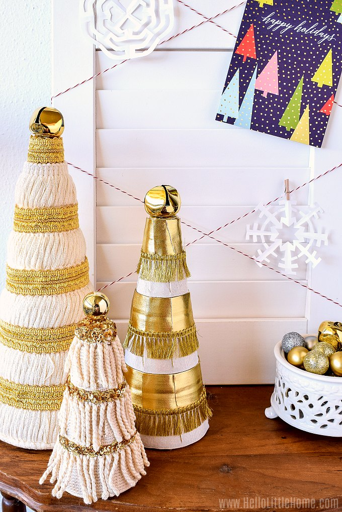 A DIY Christmas Card Display with homemade mini Christmas trees in front.