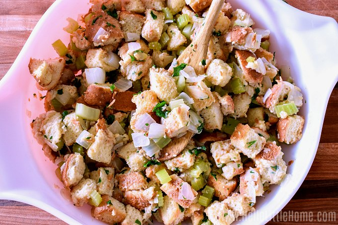 Mixing stuffing ingredients together in a large bowl.