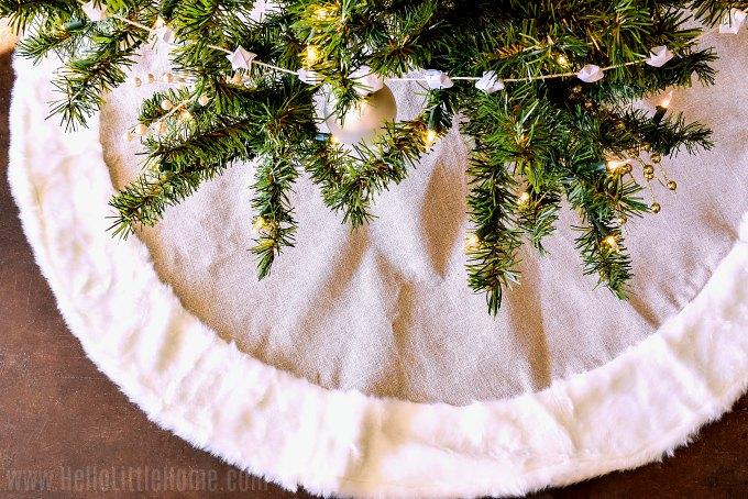 Adding a tree skirt to the Christmas tree.