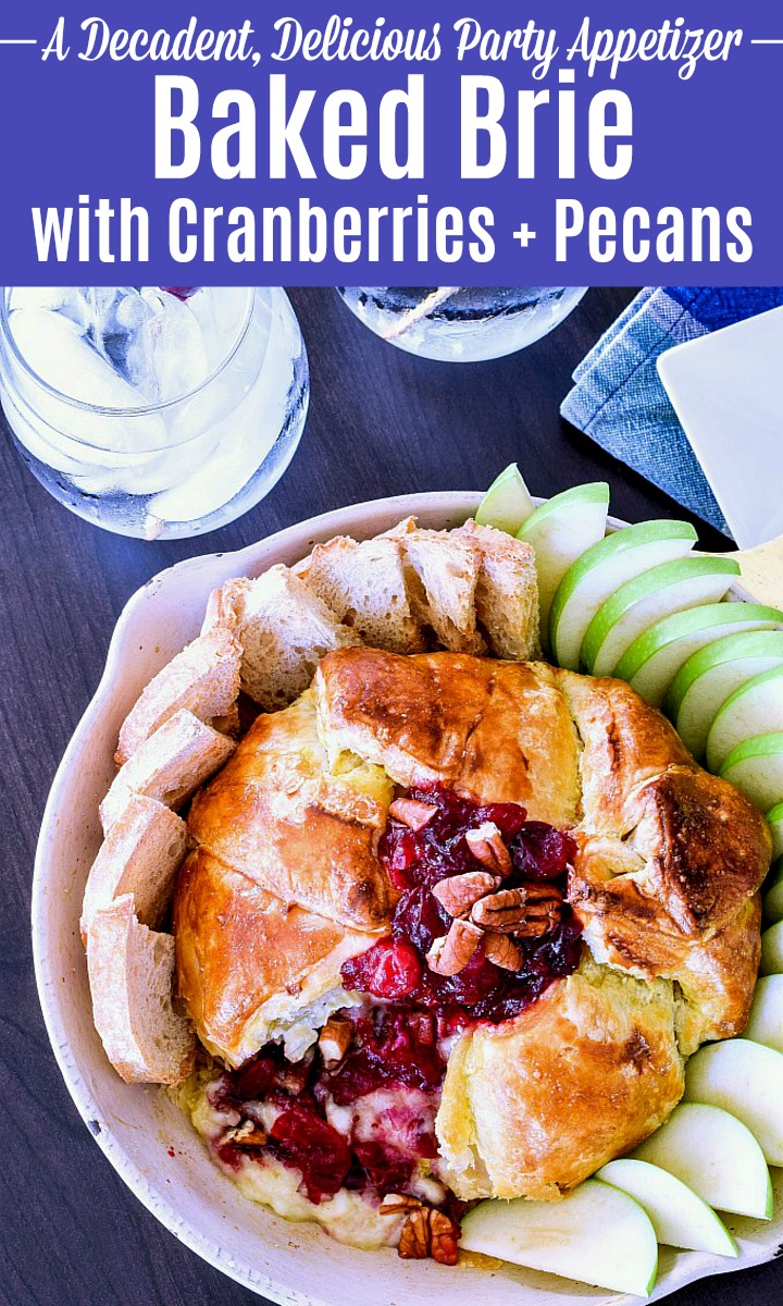 Baked Brie with Cranberries and Pecans in a baking dish surrounded by apples and bread slices.