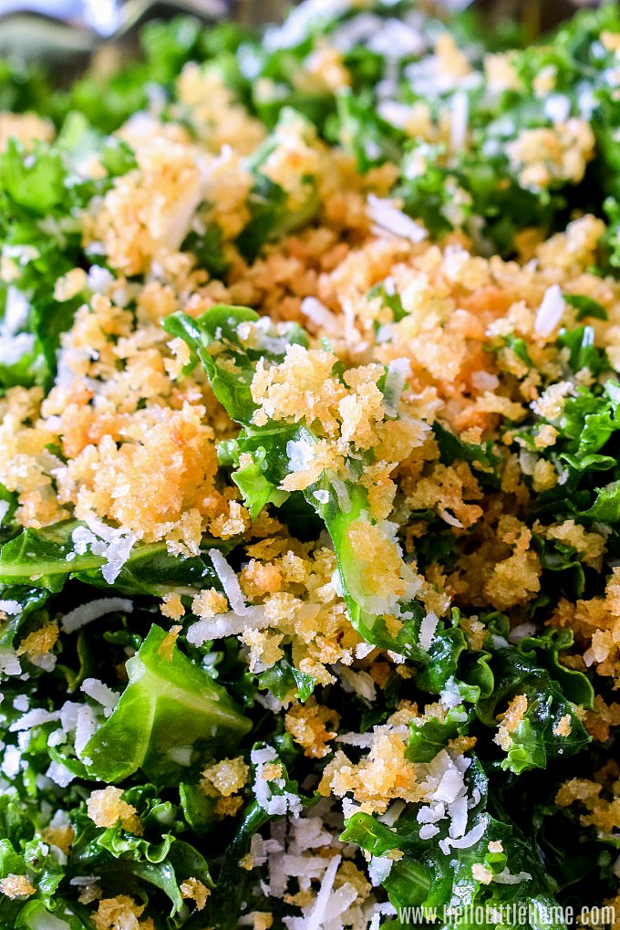 Closeup of a Lemon Kale Salad topped with bread crumbs and Parmesan cheese.