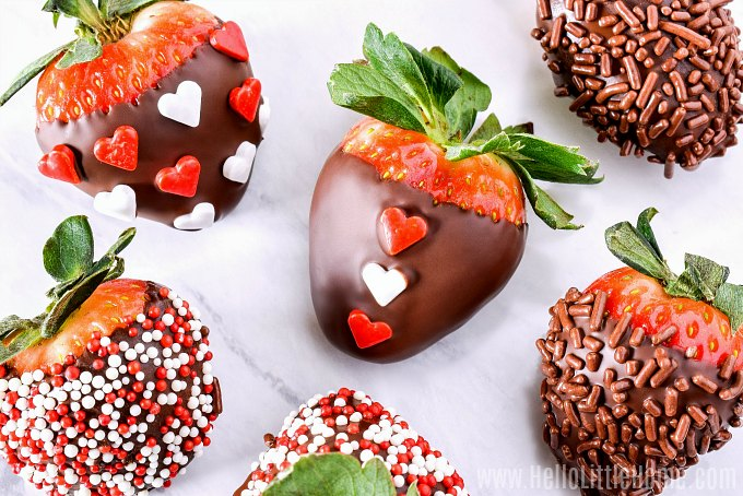 Different types of chocolate covered strawberries decorated with sprinkles arranged on a marble counter.
