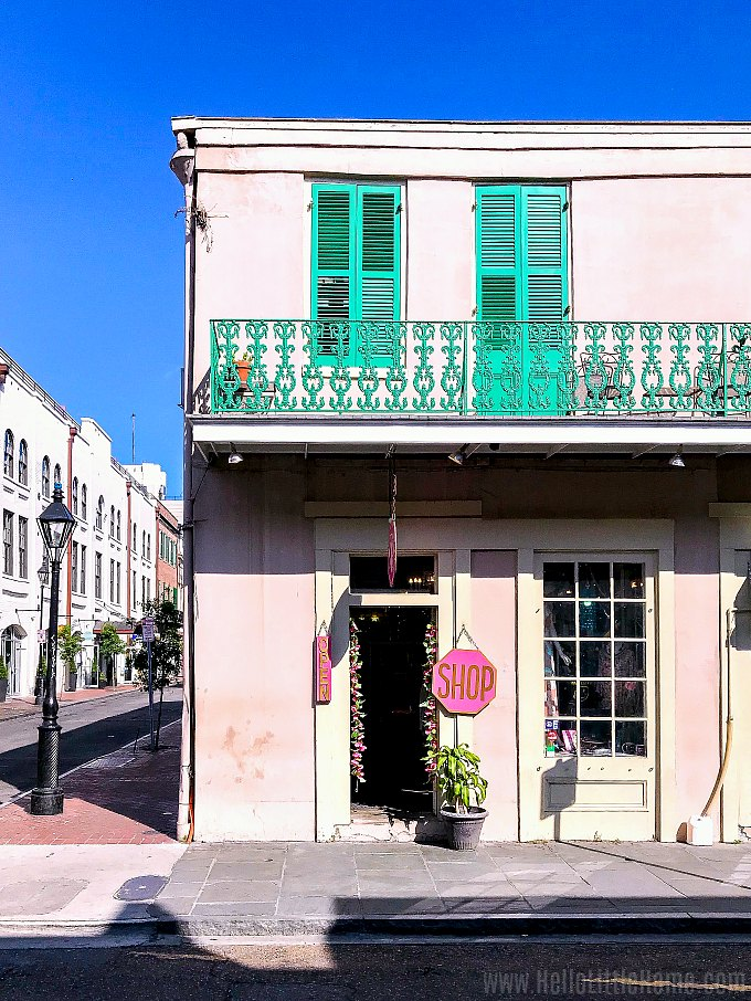 A pink building with green balcony in the French Quarter.