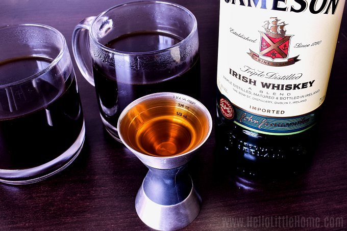 A jigger filled with Jameson Irish whiskey with two mugs of coffee in the background.