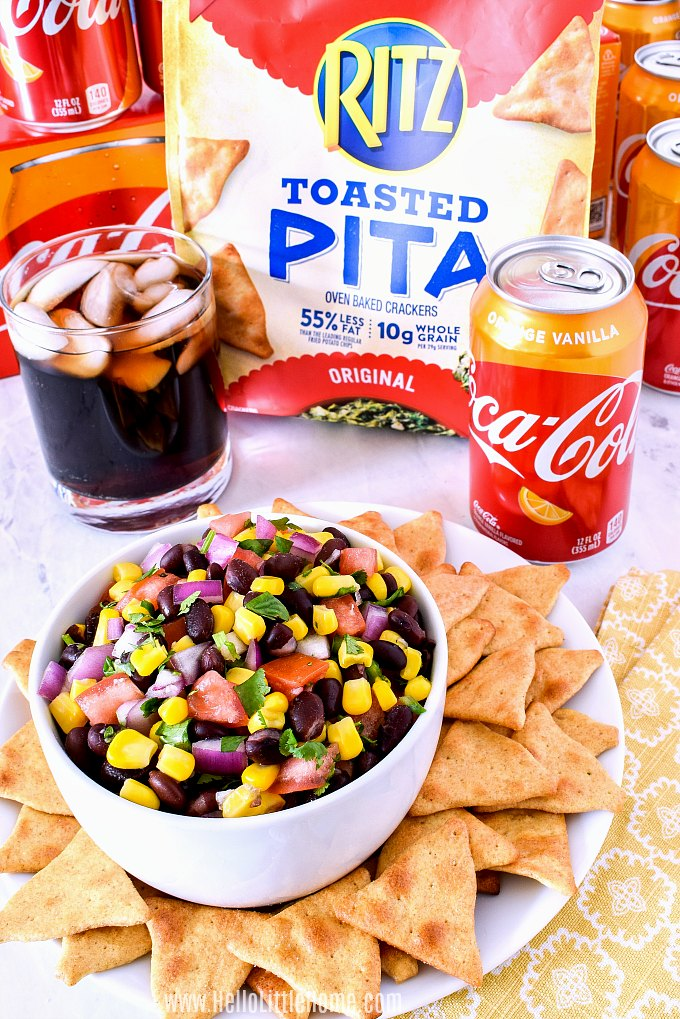 A bowl of Black Bean and Corn Salsa served with Ritz Toasted Pita and Orange Vanilla Coca-Cola.
