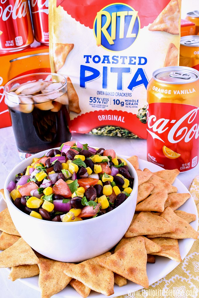 A bowl of Black Bean and Corn Salsa with soda and a bag of pita chips in the background.