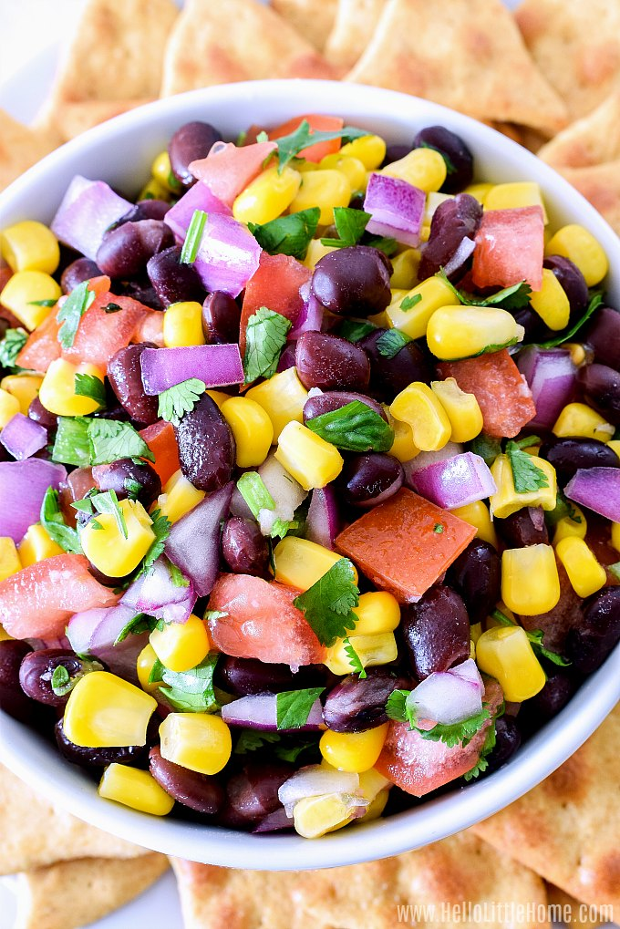 Closeup of a bowl of Black Bean Corn Salsa surrounded by chips.