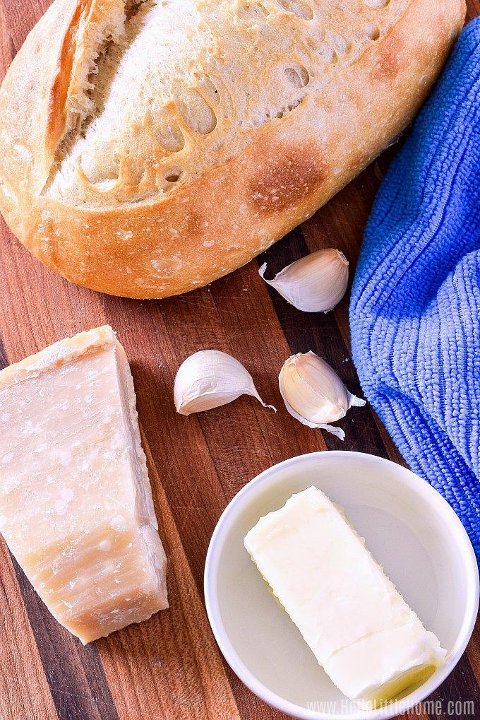 Garlic bread ingredients on a wood cutting board: butter, parmesan cheese, fresh garlic, Italian bread.