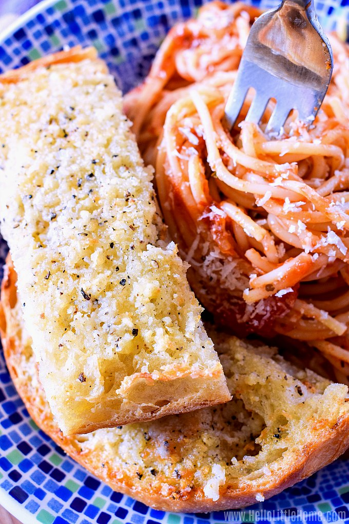 Two slices of garlic bread served with a bowl of pasta.