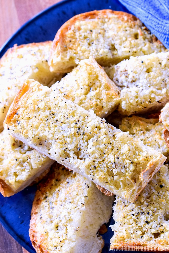 A blue plate covered with slices of garlic toast.