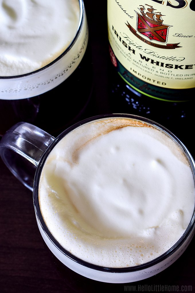 An overhead photo of two mugs of Irish Coffee topped with whipped cream and a bottle of whiskey.