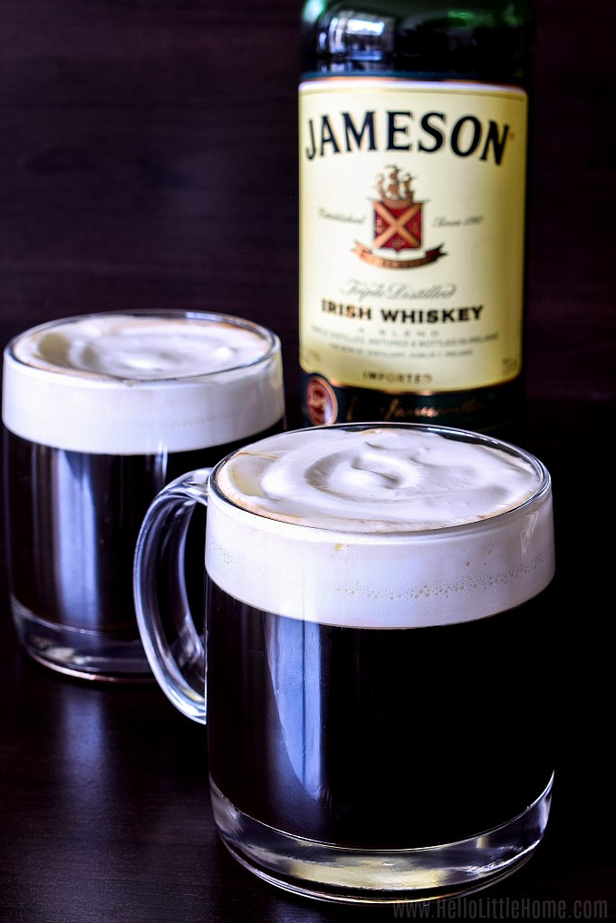 Two mugs of Irish Coffee topped with whipped cream, with a bottle of Jameson Irish whiskey in the background.