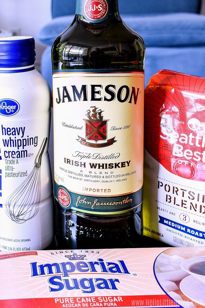Irish Coffee Ingredients on a table: sugar cubes, heavy cream, Irish whisky (Jameson), and coffee.