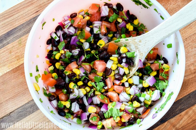 Mixing together ingredients for Black Bean and Corn Salsa in a large bowl.