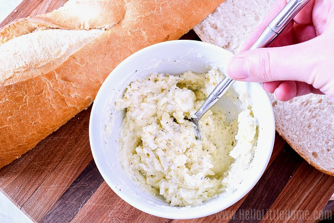 Mixing together garlic bread spread ingredients in a small bowl.
