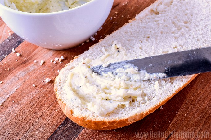 Using a knife to spread bread with Garlic Butter.