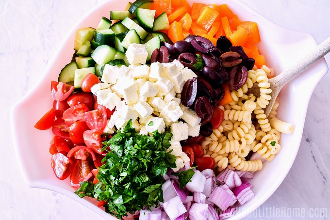 Veggies, olives, feta, and other Greek Pasta Salad ingredients in a bowl before mixing.