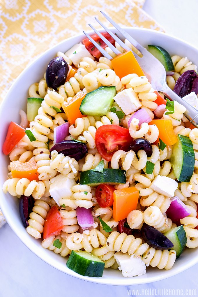 A bowl of easy Greek Pasta Salad with a fork in it.