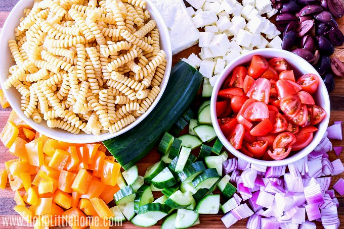 Greek Pasta Salad ingredients: pasta, peppers, cucumber, onions, tomatoes, olives, and feta cheese.