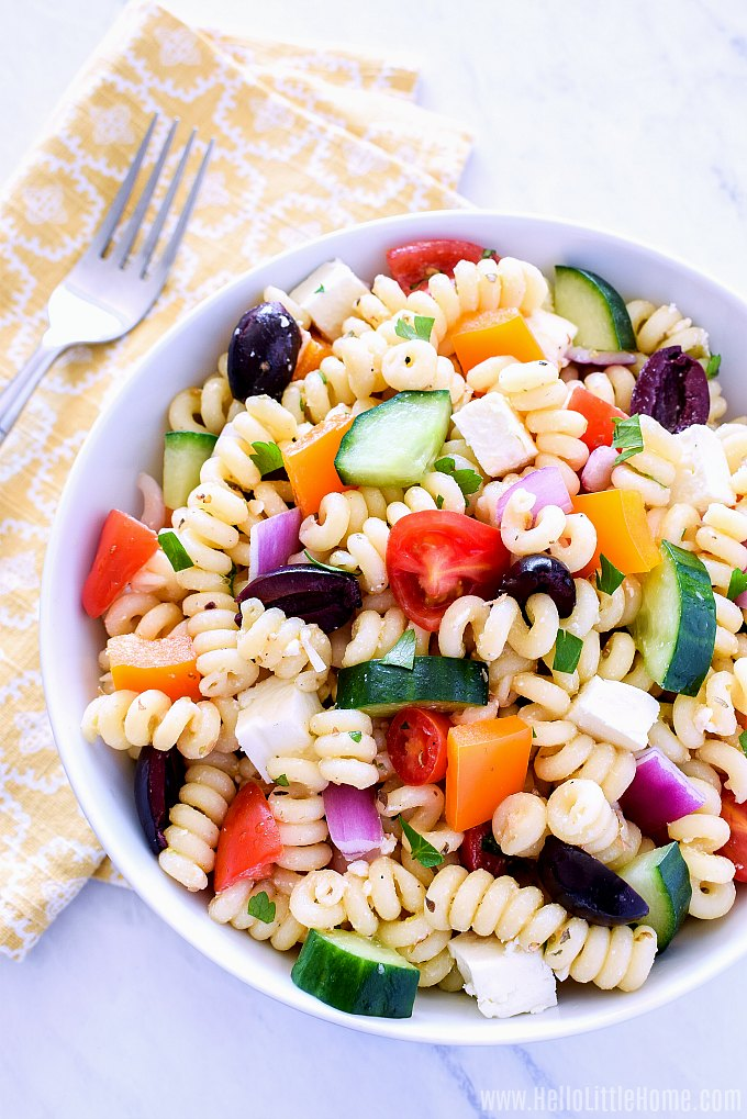 A white bowl filled with healthy Greek Pasta Salad.