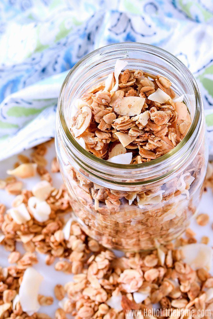 Homemade granola in a mason jar with a blue napkin in the background.