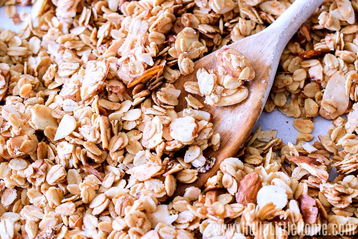 A pan covered with homemade granola and a wood spoon.