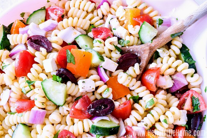 Mixing together ingredients for Greek Pasta Salad in a big bowl.