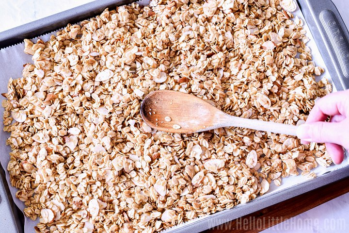 Pressing oats with a wood spoon to make chunky granola.