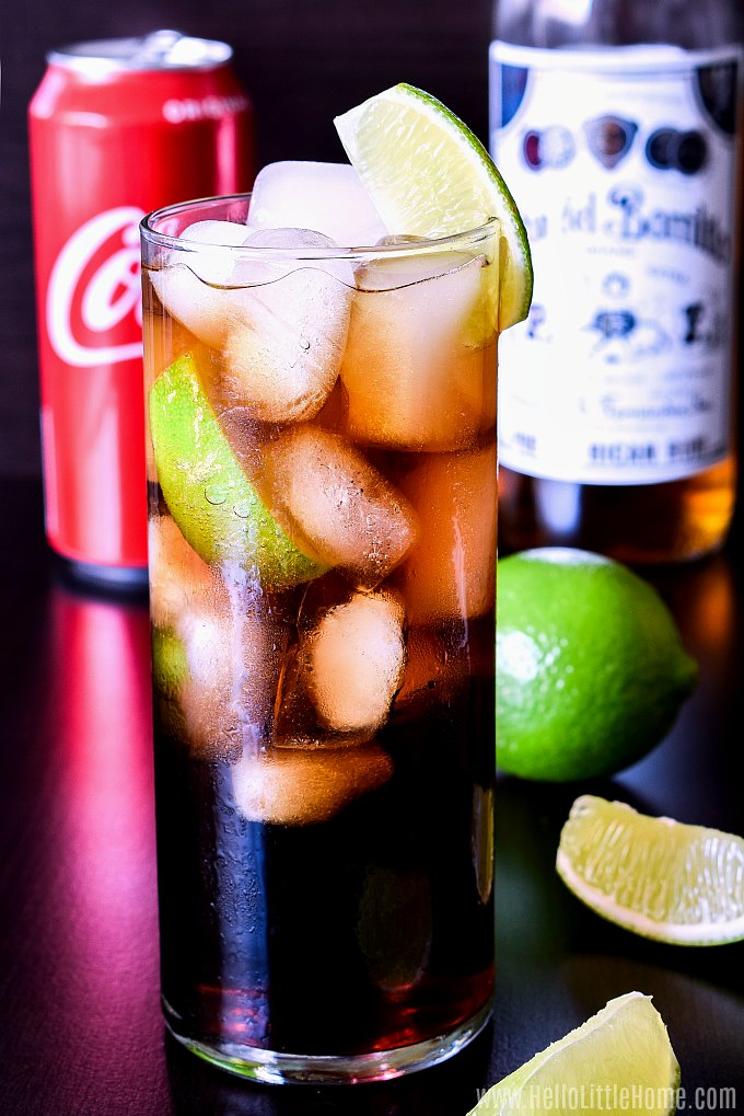 A Rum and Coke on a table with lime wedges.