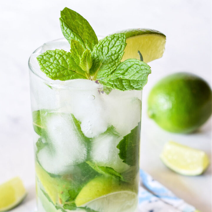 Closeup of a classic Mojito served in a tall glass with a lime in the background.