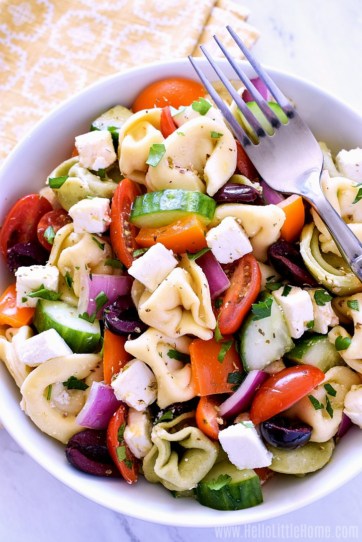 A Greek Tortellini Salad recipe served in a white bowl.