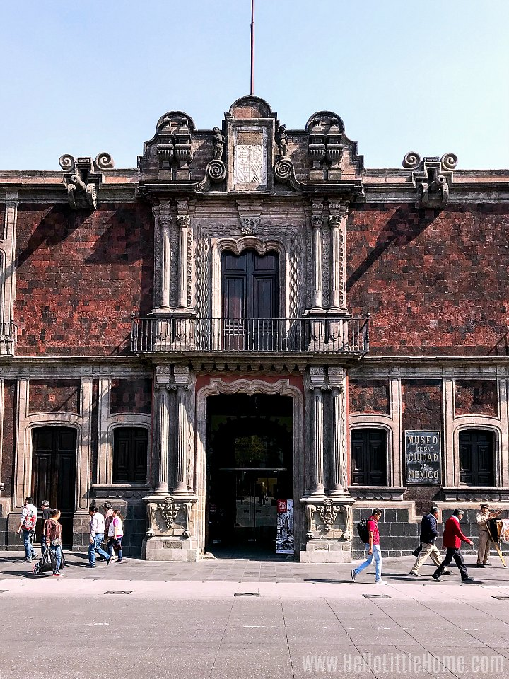 People walking by the exterior of the Museum of the City of Mexico.