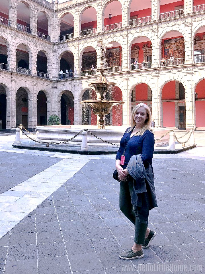 A woman standing in the courtyard of the National Palace in Mexico City.
