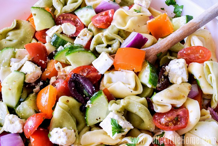 A wood spoon in a bowl of the tortellini pasta salad.
