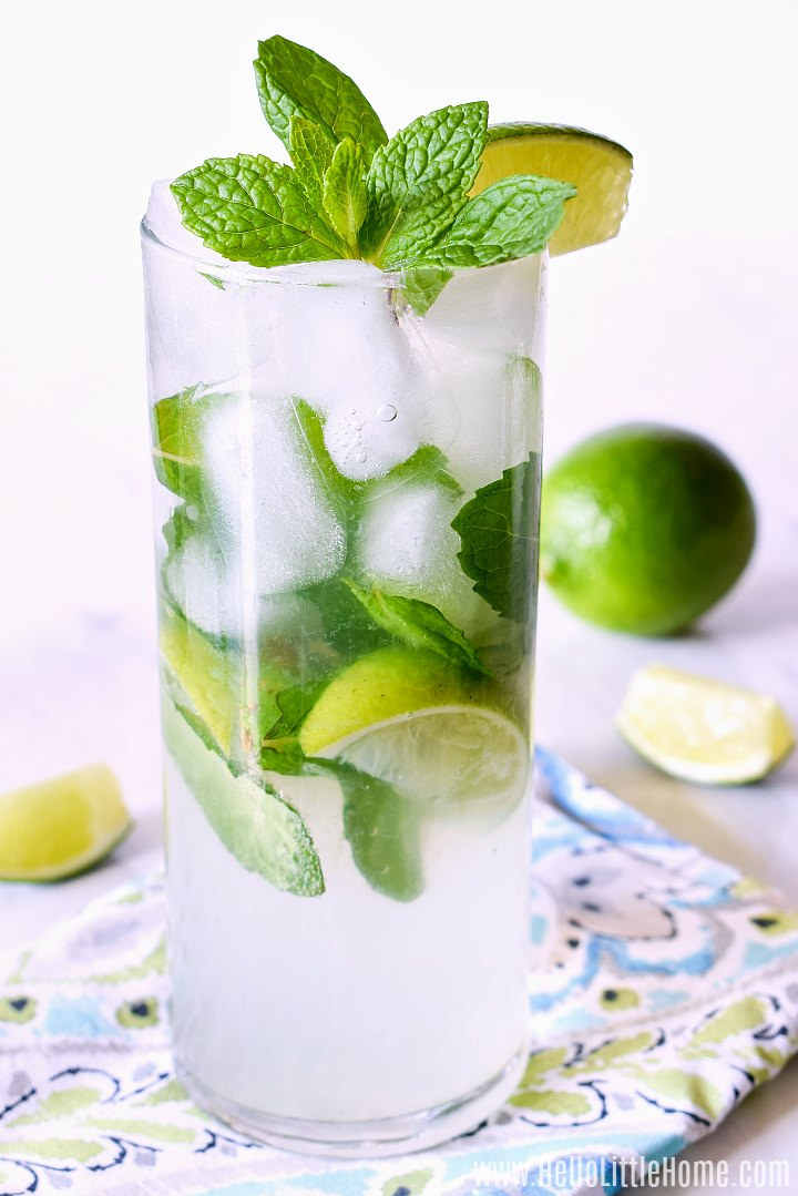 A Mojito cocktail with a lime in the background.