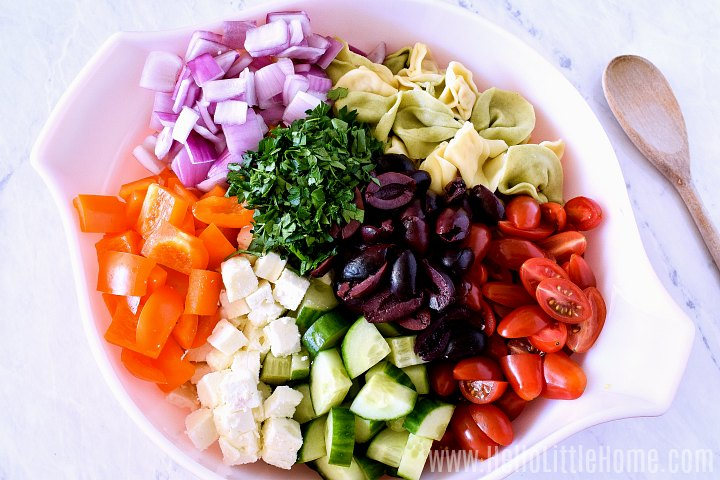 Tortellini Salad ingredients layered together in a large bowl.