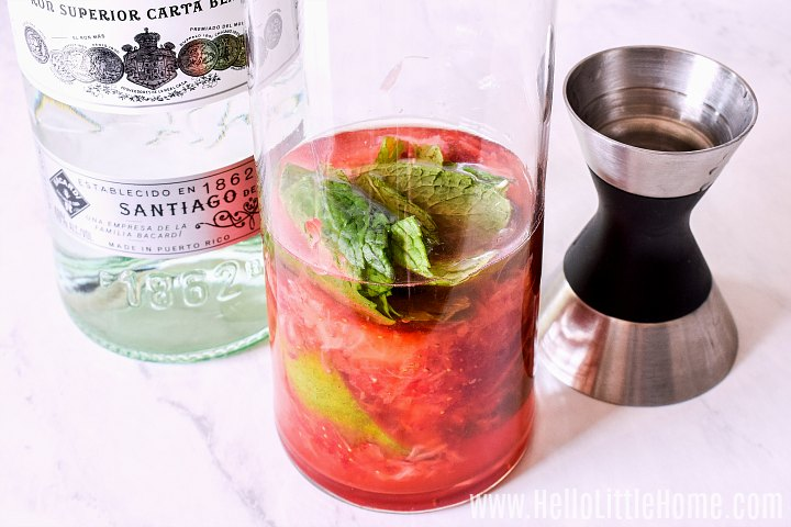 Adding rum to a glass filled with strawberries, lime, and sugar.