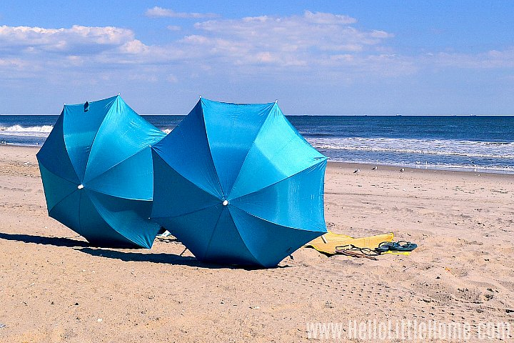 Two chair with blue umbrellas on the beach.